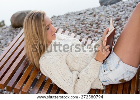Young woman sitting on bench, on stone beach and reading a book. - stock photo