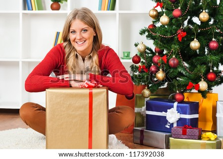 Young woman sitting on carpet with big Christmas present,Christmas presents - stock photo