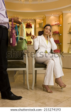 Young woman sitting on chair in glamorous boutique, male shop assistant showing her selection of designer handbags, woman using mobile, pointing