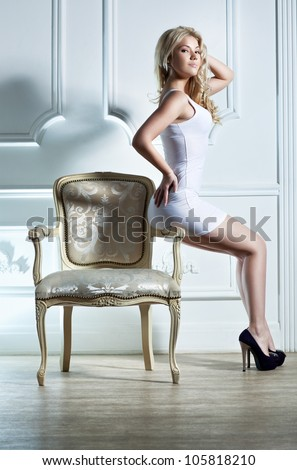Young woman sitting on chair on white wall background. - stock photo