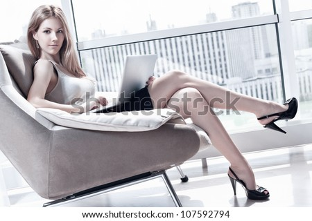 Young woman sitting on chair with laptop. Bright white colors. - stock photo