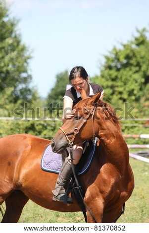 Young woman sitting on chestnut horse - stock photo