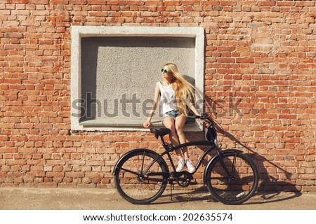 Young woman sitting on city bicycle near brick wall. Outdoor lifestyle portrait of girl with cruiser. - stock photo