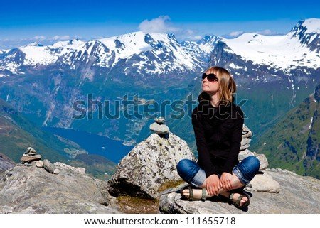 Young woman sitting on cliff and enjoy the view - stock photo