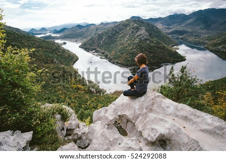 Young woman sitting on cliff's edge and looking to beautiful view