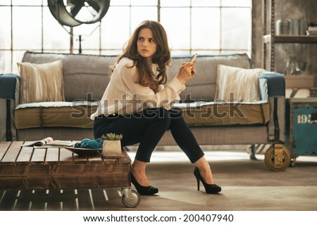 Young woman sitting on coffee table in loft apartment - stock photo