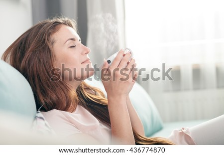Young woman sitting on couch at home and drinking coffee, casual style indoor shoot - stock photo