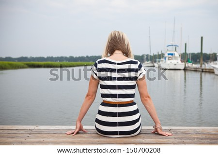 Young woman sitting on dock looking at water. - stock photo
