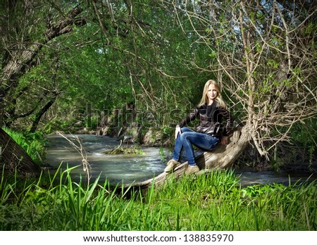 Young woman sitting on dried-up tree over a pond