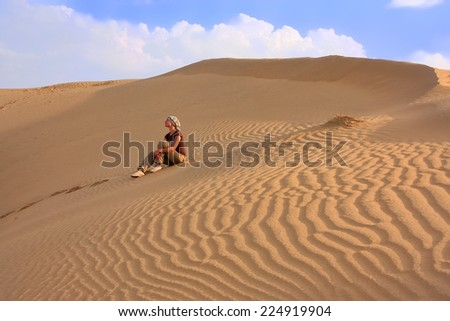Young woman sitting on dunes, Thar desert, Jaisalmer, Rajasthan, India - stock photo