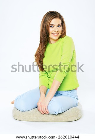 Young woman sitting on floor. Isolated white background full body portrait of young female model with long hair. - stock photo