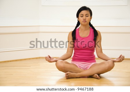 Young woman sitting on floor meditating in yoga lotus pose with legs crossed and eyes closed. - stock photo