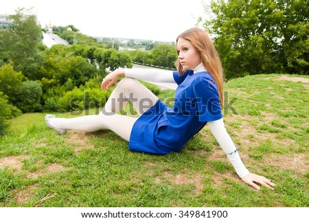 Young woman sitting on grass in city park - stock photo