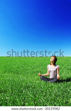 Young woman sitting on green grass
