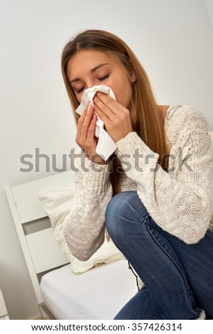 Young woman sitting on her bed and sneezing