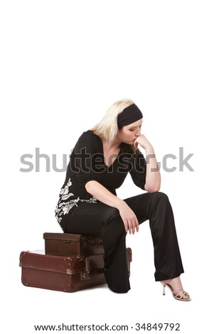 Young woman sitting on old fashioned suitcases