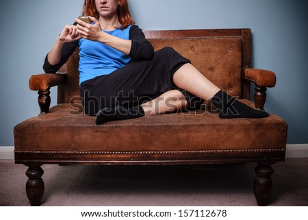 Young woman sitting on old sofa texting on her phone - stock photo