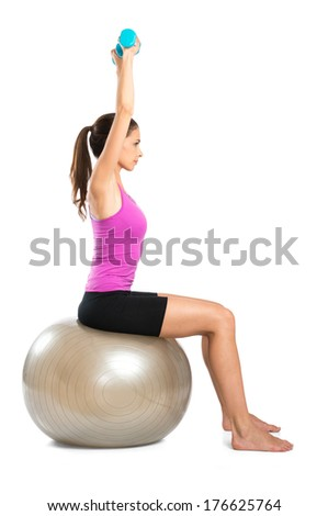 Young Woman Sitting On Pilate Ball And Exercising With Dumbbells Isolated On White Background