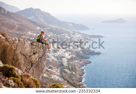 Young woman sitting on rock and enjoying beautiful view - stock photo