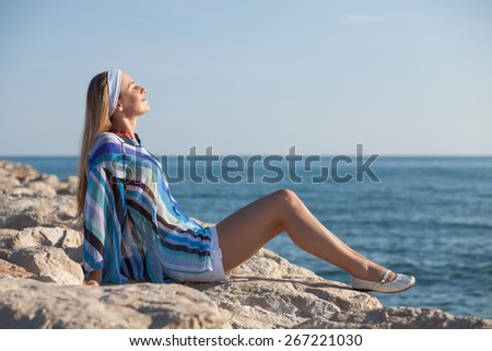 Young woman sitting on rock and enjoying sun