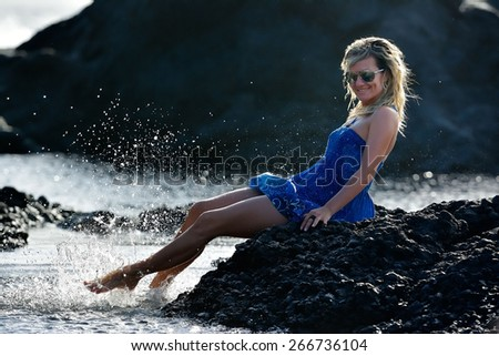 young woman sitting on rocky beach in summer