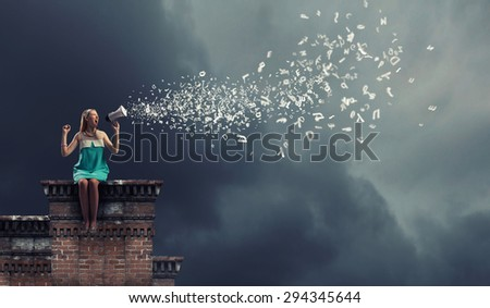 Young woman sitting on roof and screaming in megaphone - stock photo