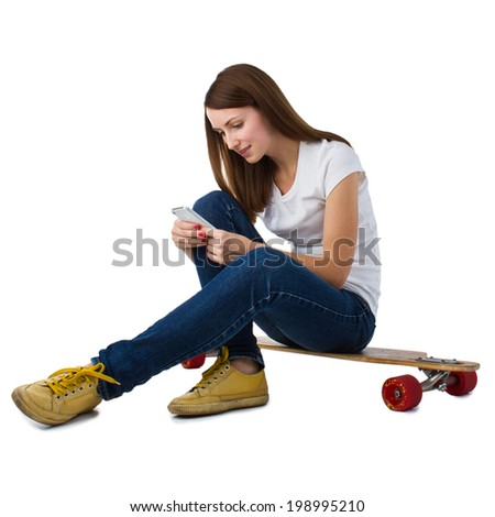 Young woman sitting on skateboard and using smart phone. Isolated on a white background. - stock photo