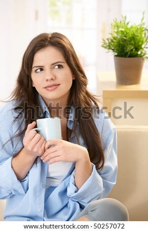 Young woman sitting on sofa at home drinking morning coffee, smiling.