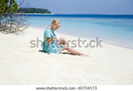 Young woman sitting on the beach and playing with sand.
