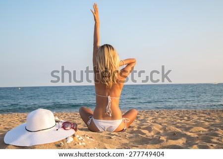 young woman sitting on the beach in bikini and relaxing - stock photo