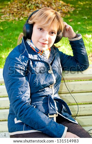 Young woman sitting on the bench and listening to music
