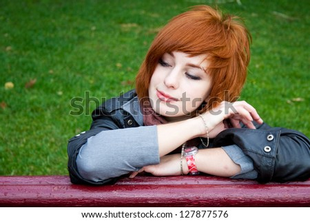 Young woman sitting on the bench in an autumn park