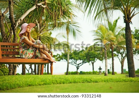 Young woman sitting on the bench in park - stock photo