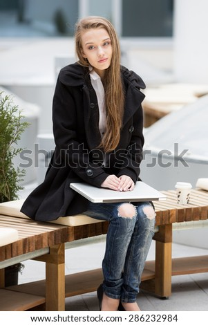 Young woman sitting on the bench with laptop. - stock photo