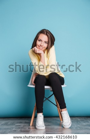 Young woman sitting on the chair hand under chin isolated on the blue background - stock photo