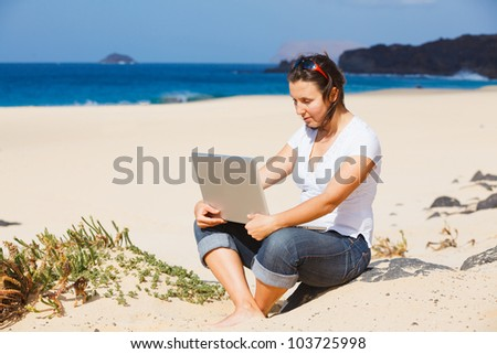 Young woman sitting on the exotic tropical beach with laptop computer - stock photo