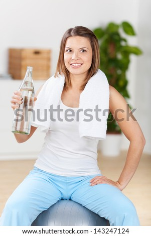 Young woman sitting on the fitness ball and holding bottled water