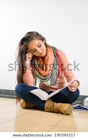 Young woman sitting on the floor and reading a book for the university