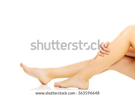 Young woman sitting on the floor and touching her legs - stock photo