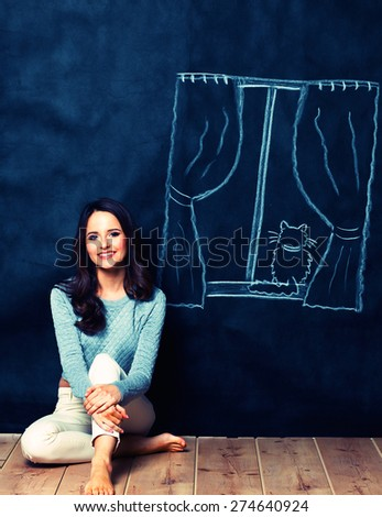 Young woman sitting on the floor near dark wall with painted a window - stock photo