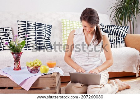 Young woman, sitting on the floor, reading from computer and eating healthy breakfast - stock photo