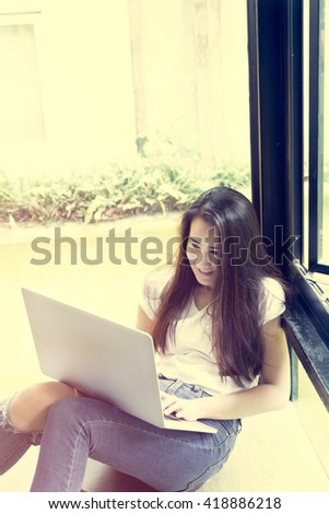 young woman sitting on the floor while using her laptop, beautiful woman smiling at you while sitting on floor in front of her laptop at home indoor-vintage tone filter effect - stock photo