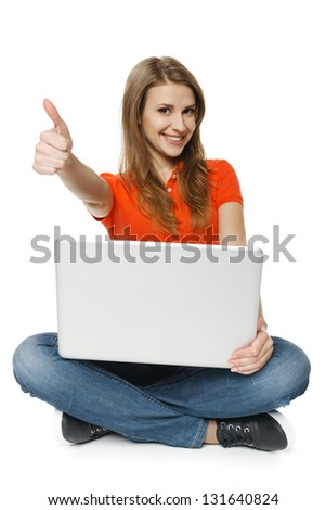 Young woman sitting on the floor with her laptop making thumb up gesture, over white background