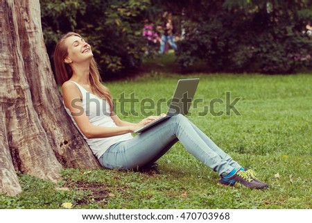 Young woman sitting on the grass and reading book outdoor. Vintage filtered image.