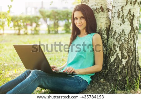 Young woman sitting on the grass and using laptop and typing.