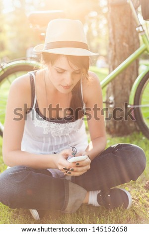 Young woman sitting on the grass and using smart phone. - stock photo