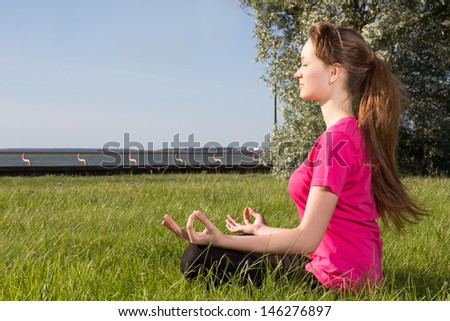 Young woman sitting on the grass in park