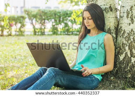 Young woman sitting on the grass, using laptop and typing.