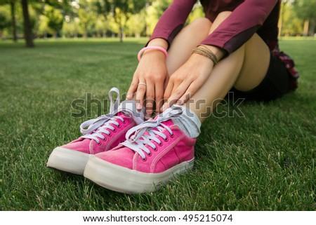 Young woman sitting on the green grass in pink sneakers