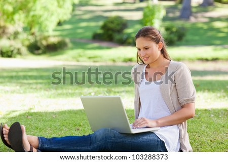 Young woman sitting on the lawn with her laptop